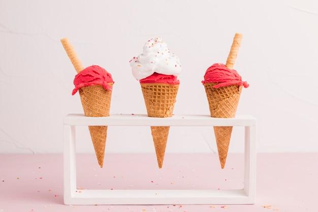 Cucharada de helado congelado rojo en conos con paja de gofres