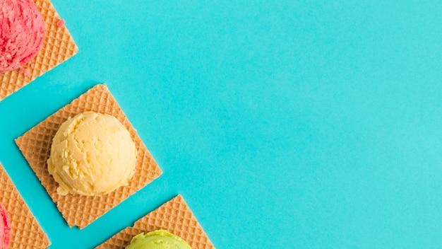 Cucharada de helado congelado en waffles en superficie turquesa