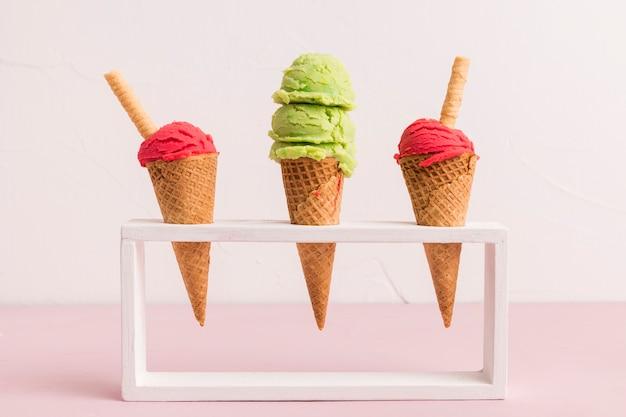 Cucharada de helado fresco en conos con paja de waffle en soporte
