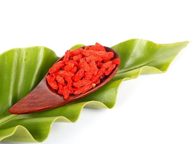 Cucharada de madera de bayas de goji secas en hojas de helechos