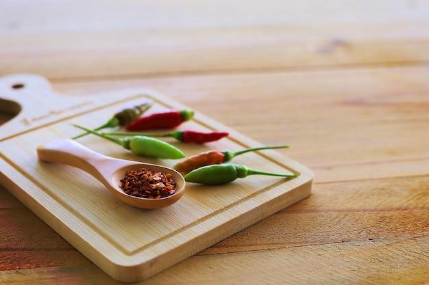 Cucharada de pimienta de cayena y chile fresco sobre madera