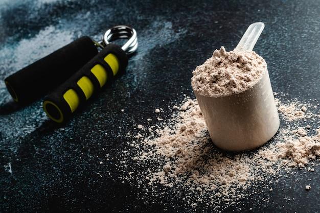 Cucharada de proteína de suero en. nutrición deportiva.