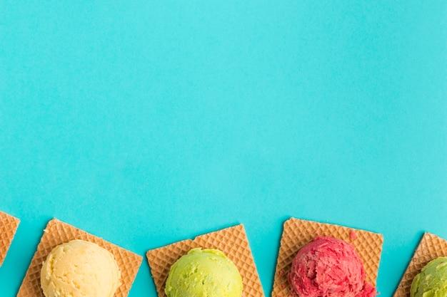 Cucharada sabrosa del helado en los waffles cuadrados en superficie de la turquesa