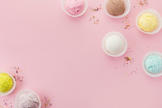 Cucharadas de helado de colores en vasos de papel