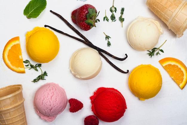 Cucharadas del helado de la naranja, de la vainilla, de la frambuesa y de fresa en el fondo blanco