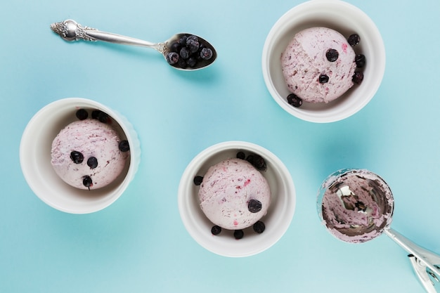 Cucharadas de helado en tazas blancas