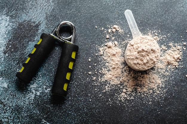 Cucharadas llenas de proteínas en polvo para nutrición física para comenzar a entrenar