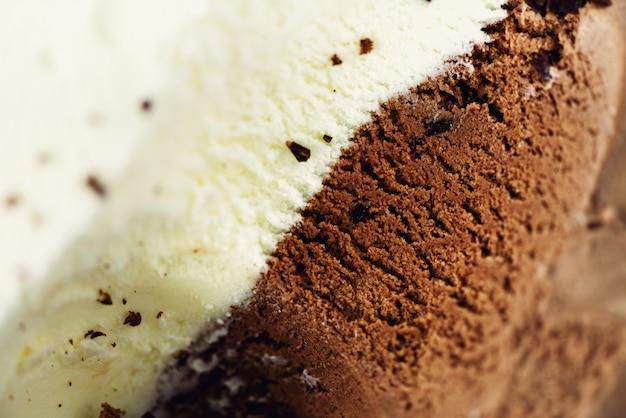 Cucharadas de vainilla y helado de chocolate. postre de yogur dulce o textura de helado marrón.