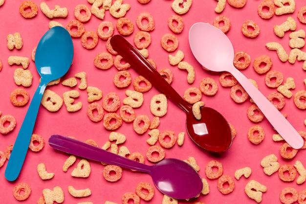 Cucharas coloridas rodeadas de bucles de frutas de cereales