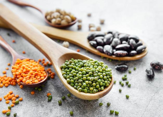 Cucharas con diferentes tipos de legumbres en un escritorio de hormigón gris