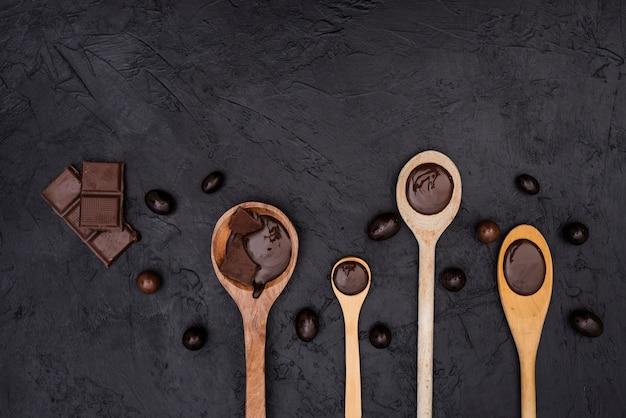 Cucharas de madera con jarabe de chocolate y barras de chocolate.