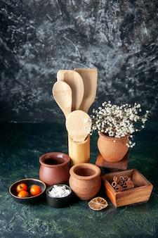 Cucharas de madera de vista frontal con ollas y canela en el color de la pared oscura, condimento, cubiertos de comida con sal