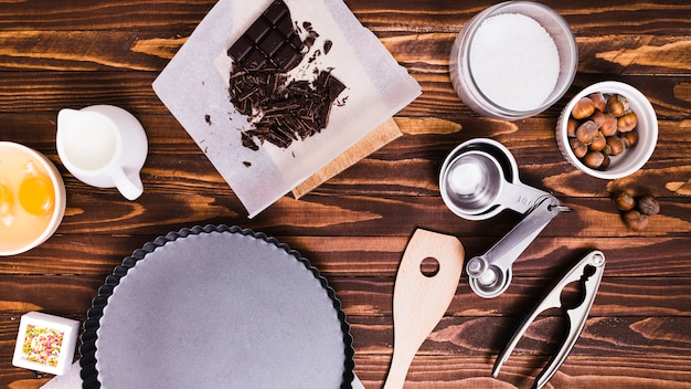 Cucharas medidoras; barra de chocolate; leche; yema; plato de avellanas y hornear sobre fondo con textura madera