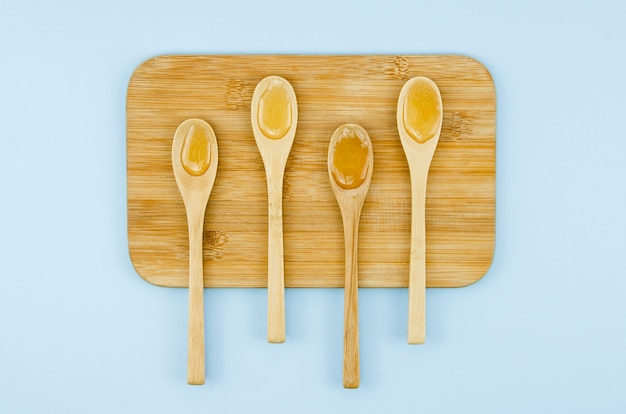Cucharas con miel en la vista superior del armario