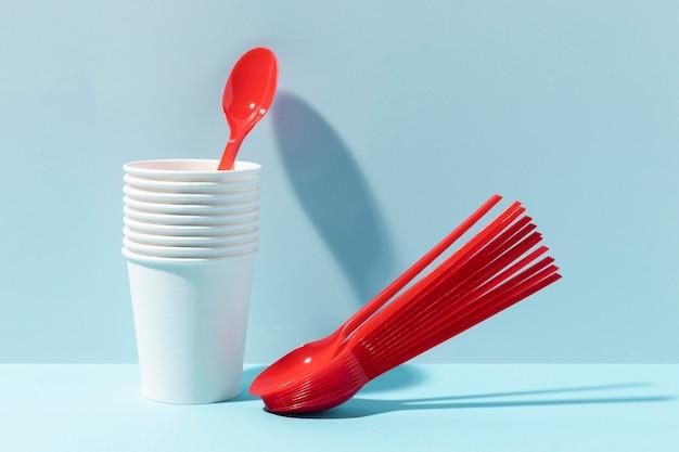 Cucharas pequeñas rojas y vasos de plástico