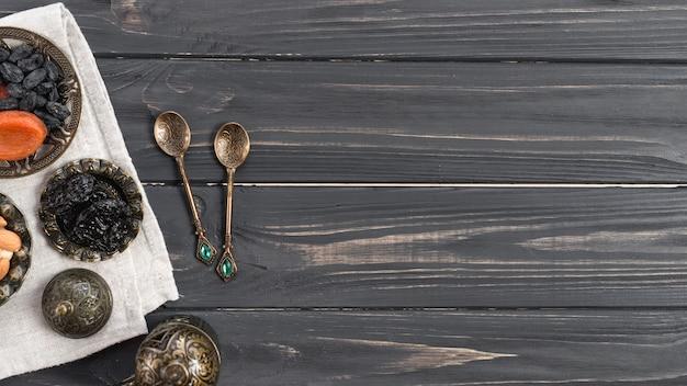 Cucharas turcas metálicas con dátiles secos; pasas sobre el escritorio de madera