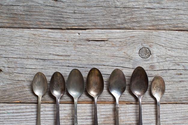 Cucharas vintage con pátina sobre mesa de madera antigua