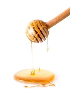 Cucharón de madera con miel sobre fondo blanco