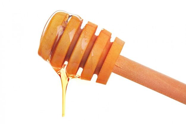 Cucharón de miel con miel que fluye