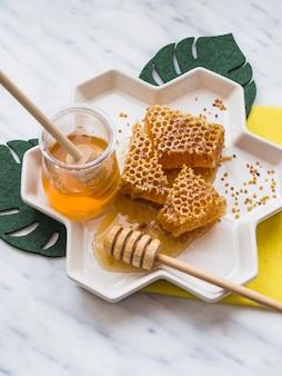 Cucharón de miel y panal con polen de abeja en bandeja blanca sobre fondo de mármol