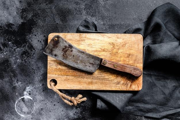 Cuchilla de carne en la vieja tabla de cortar de madera rayada. fondo oscuro vista superior.