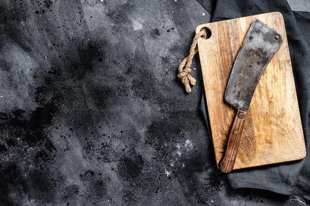 Cuchilla de carne en la vieja tabla de cortar de madera rayada. vista superior.