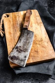 Cuchilla de carne en la vieja tabla de cortar de madera rayada.