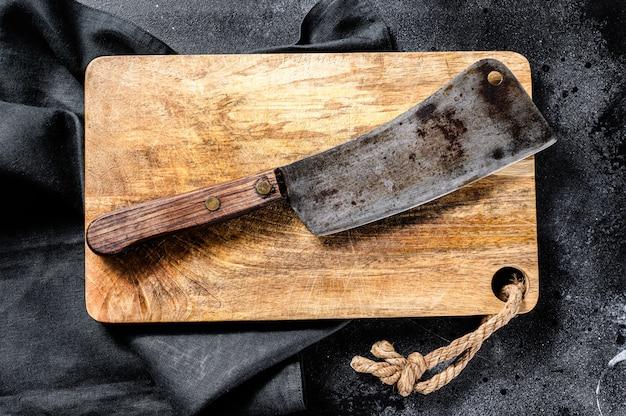 Cuchilla de carnicero vintage sobre tablero de hormigón.