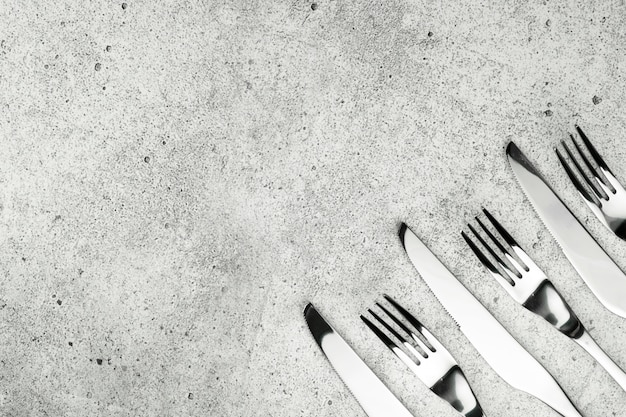 Cuchillería. tenedores y cuchillos sobre un fondo de hormigón ligero.