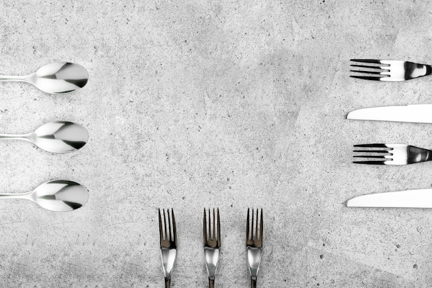 Cuchillería. tenedores y cuchillos sobre fondo de marco de hormigón ligero.
