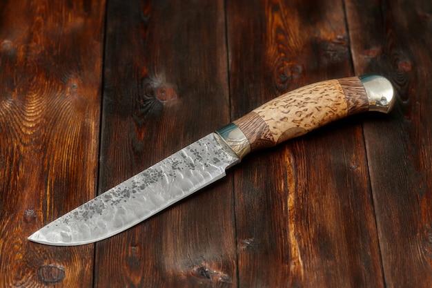Cuchillo de acero de caza damasco hecho a mano sobre superficie de madera