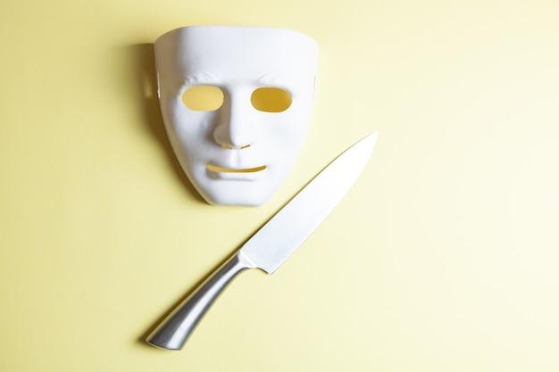 Cuchillo de acero y máscara sobre fondo amarillo