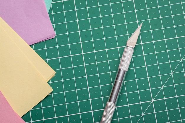 Cuchillo afilado para cortar papel en una estera de corte cerca de papeles de colores para origami