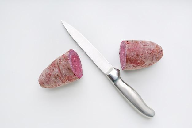 El cuchillo afilado cortó patatas dulces a medias púrpuras en el fondo blanco.