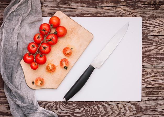 Cuchillo afilado y manojo de tomates cherry en una tabla de cortar sobre el papel blanco contra el escritorio