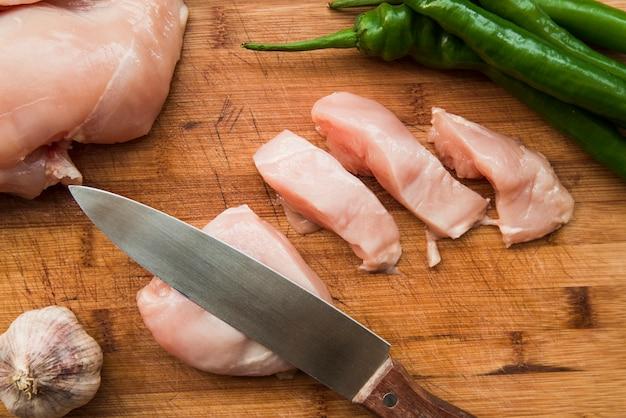 Cuchillo afilado y rodajas de pollo crudo en una tabla de cortar con ajo y chile verde