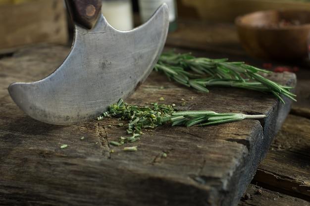 Cuchillo afilado y romero sobre una tabla de madera de rutina