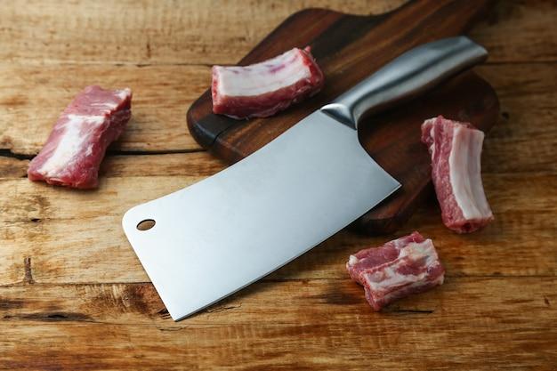 Cuchillo cuchilla y costillas en la tabla de madera