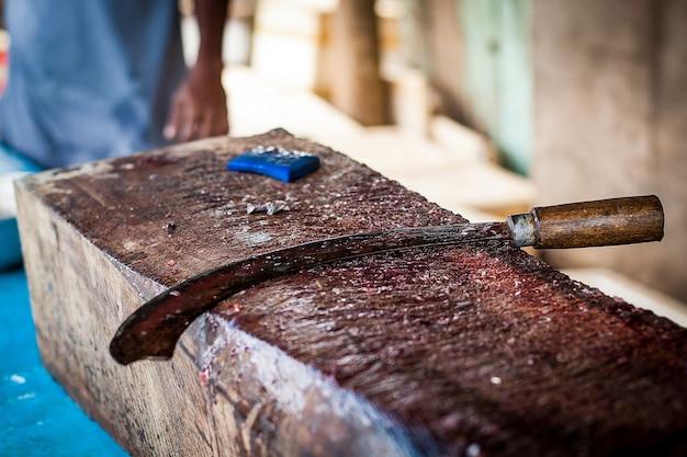 Cuchillo curvo para cortar pescado en la tabla de cortar.