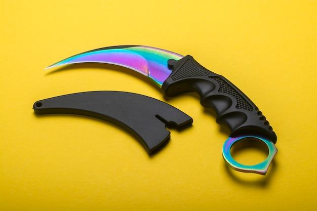 Cuchillo karambit sobre un fondo amarillo cerrar