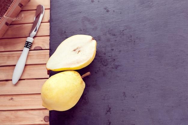 Cuchillo y peras cortadas por la mitad yacen sobre un fondo de madera