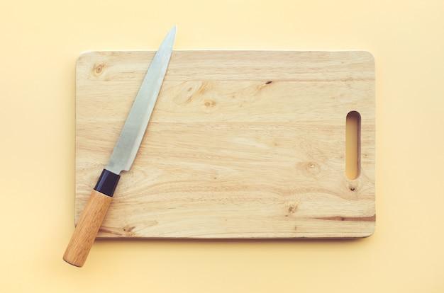 Cuchillo sobre tabla de cortar de madera sobre fondo de color pastel