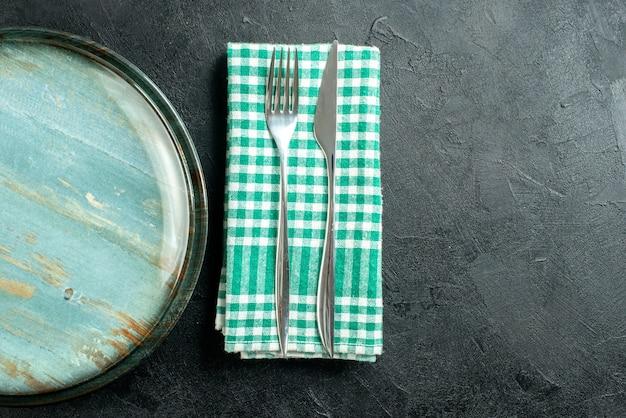 Cuchillo y tenedor de cena de plato redondo de la mitad superior vista en una servilleta a cuadros verde y blanca en el lugar de copia de mesa negra