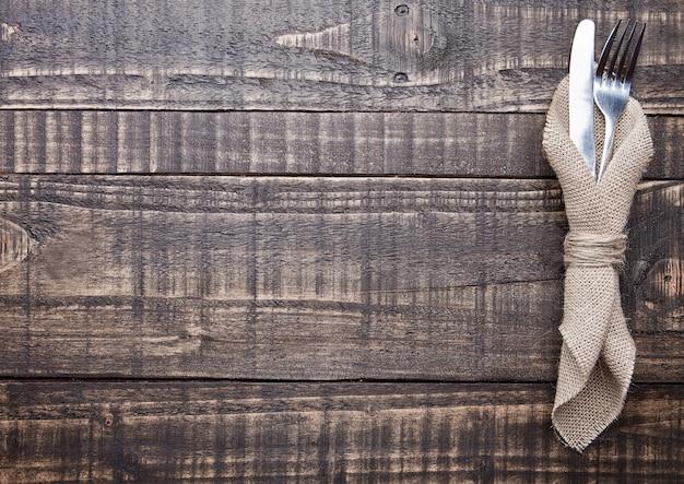Cuchillo y tenedor dentro de toalla de cocina sobre tabla de madera