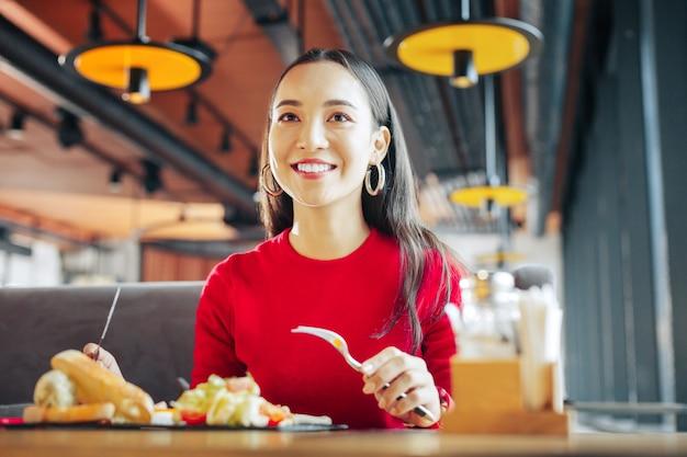 Cuchillo y tenedor empresaria con buen maquillaje sosteniendo cuchillo y tenedor mientras almuerza
