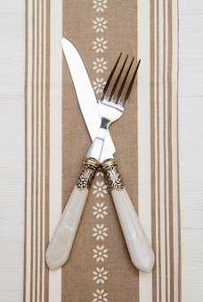 Cuchillo y tenedor en servilleta sobre fondo de madera blanco