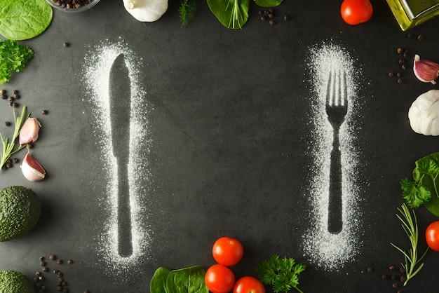 Cuchillo y tenedor silueta hecha con harina sobre fondo oscuro