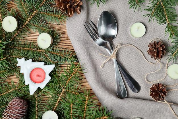 Cuchillo y tenedor sobre una servilleta sobre fondo de madera con accesorios de navidad