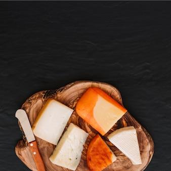 Cuchillo y trozos de queso en la madera