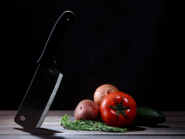 Cuchillo y verduras en mesa de madera